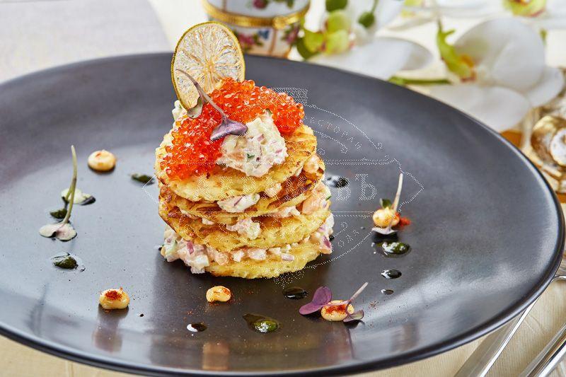 Potato pancakes with a salad of Atlantic salmon and red caviar