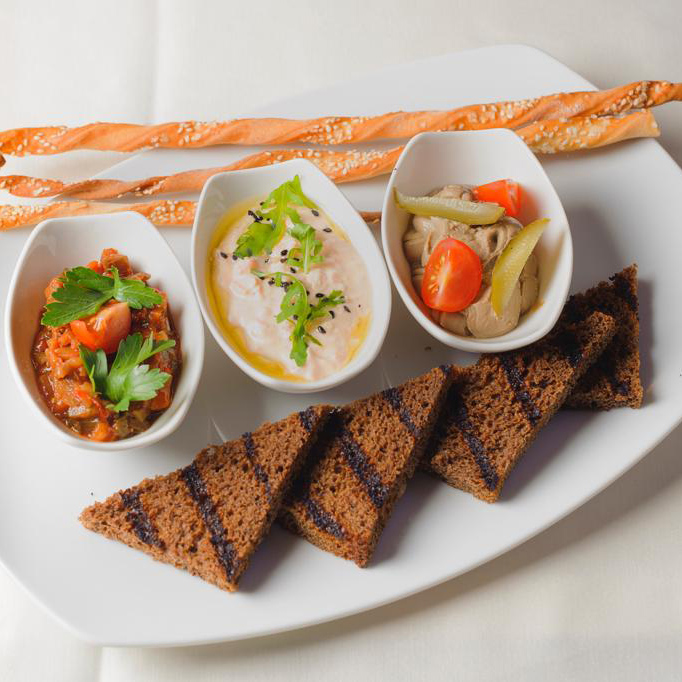 Spreads served with wine with grissini bread sticks and grilled bread (Atlantic salmon rillette, rabbit liver pate, eggplant caviar)