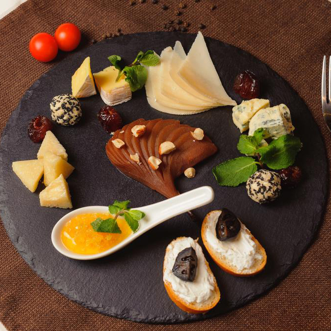 Cheese platter with honeycombs and pear in wine (Camembert, Dor Blue, Parmesan, soft Chevre, hard Frico, soft cream cheese)