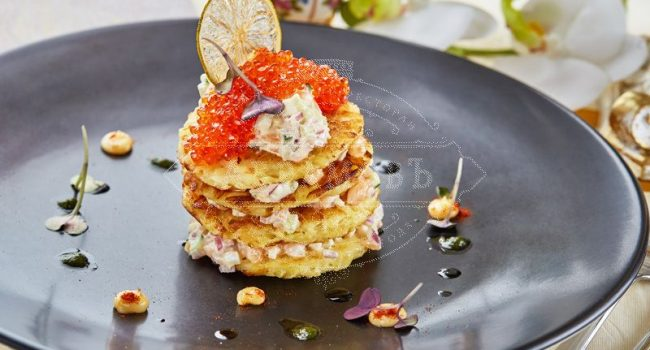 Potato pancakes with a salad of Atlantic salmon and red caviar