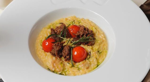 Orzo with stewed wild elk. risotto pasta with cepe mushrooms and stewed wild elk meat accompanied by cherry tomatoes and parmesan