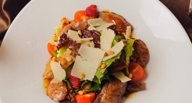 Salad with rabbit liver, cepe mushrooms, fresh raspberries sprinkled with pine nuts